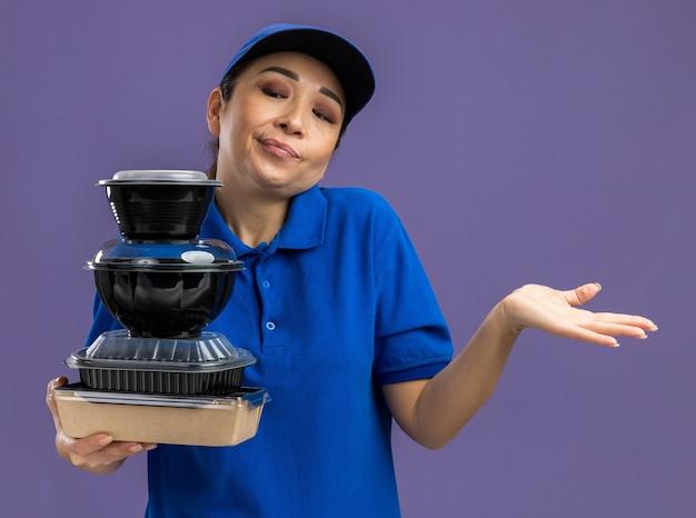 Giovane donna delle consegne in uniforme blu e berretto che tiene una pila di pacchi di cibo guardandoli confusi alzando le spalle senza risposta in piedi sul muro viola