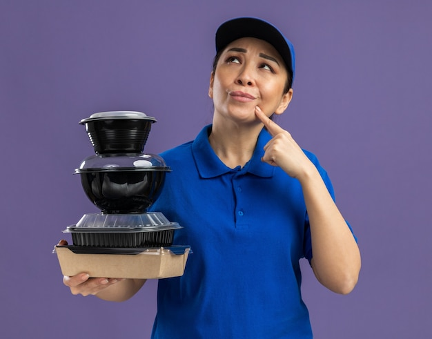 Giovane donna delle consegne in uniforme blu e berretto con una pila di pacchi di cibo che guarda in alto perplesso