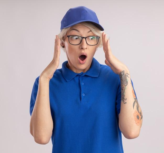 Giovane donna di consegna in uniforme blu e berretto che osserva da parte stupito e sorpreso con le braccia alzate in piedi sul muro bianco