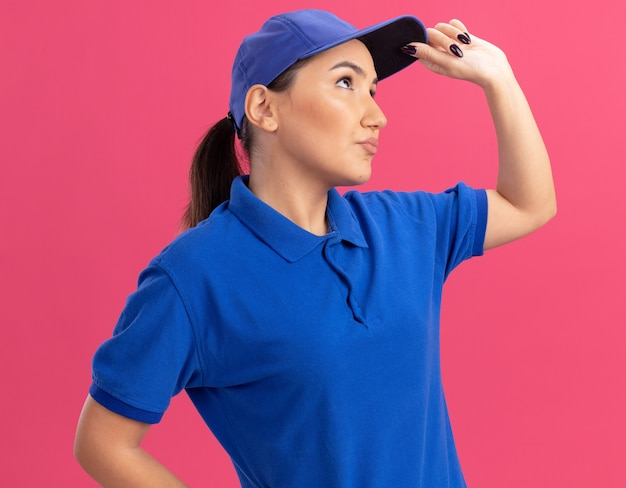 Young delivery woman in blue uniform and cap looking aside puzzled standing over pink wall