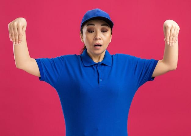 Giovane donna delle consegne in uniforme blu e berretto che guarda in basso essendo confusa gesticolando con le mani