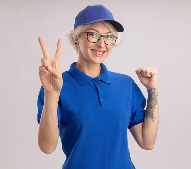 Giovane donna di consegna in uniforme blu e berretto che guarda il pugno di sollevamento che mostra il segno di v che sorride allegramente in piedi sopra il muro bianco