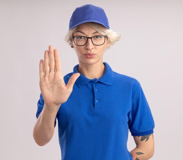 Giovane donna di consegna in uniforme blu e cappuccio che osserva con il fronte serio che mostra la mano aperta che fa il gesto di arresto che sta sopra il muro bianco