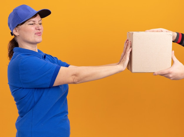 Young delivery woman in blue uniform and cap looking worried with disgusted expression refusing to take package standing over orange wall