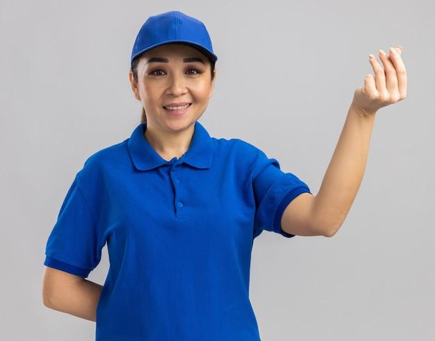 Giovane donna delle consegne in uniforme blu e berretto che fa gesto di soldi strofinando le dita sorridendo allegramente in piedi sul muro bianco