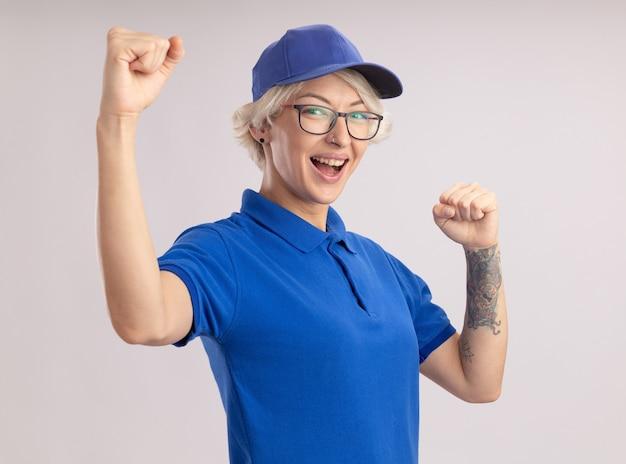 Giovane donna di consegna in uniforme blu e cappuccio che alza i pugni felici e fiduciosi in piedi sopra il muro bianco