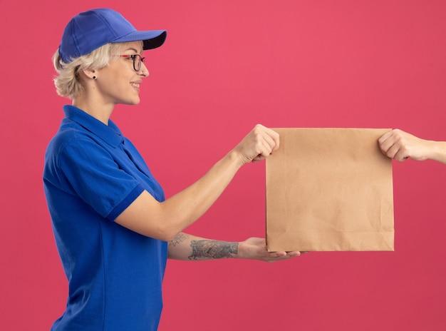 Giovane donna di consegna in uniforme blu e berretto sorridente amichevole mentre riceve il pacchetto di carta in piedi sopra il muro rosa