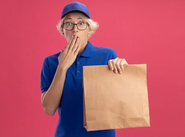 Giovane donna di consegna in uniforme blu e berretto con gli occhiali che tiene il pacchetto di carta che è scioccato che copre la bocca con la mano sulla parete rosa