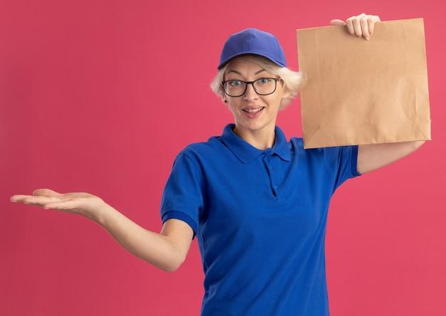Giovane donna di consegna in uniforme blu e berretto con gli occhiali che tiene il pacchetto di carta che presenta lo spazio della copia con il braccio della sua mano sopra la parete rosa
