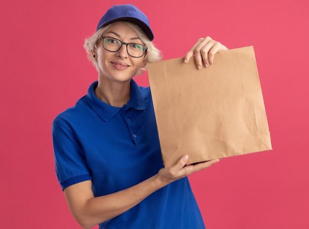 Giovane donna di consegna in uniforme blu e berretto con gli occhiali che tiene il pacchetto di carta che sorride allegramente sopra la parete rosa