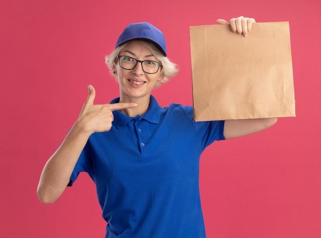 Giovane donna di consegna in uniforme blu e berretto con gli occhiali che tiene il pacchetto di carta che sorride allegramente pointign con il dito indice al pacchetto sopra la parete rosa