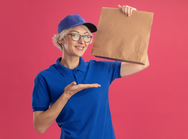 Young delivery woman in blue uniform and cap wearing glasses holding paper package  smiling cheerfully presenting with arm oh her hand over pink wall