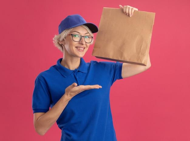 Giovane donna di consegna in uniforme blu e berretto con gli occhiali che tiene il pacchetto di carta che sorride allegramente presentando con il braccio oh la sua mano sulla parete rosa