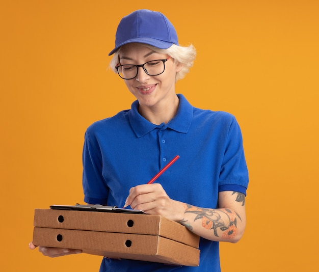 Giovane donna di consegna in uniforme blu e berretto con gli occhiali in possesso di scatole per pizza e appunti con pagine vuote che scrivono qualcosa con la matita che sorride sopra la parete arancione