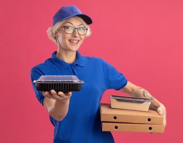 Giovane donna delle consegne in uniforme blu e berretto con gli occhiali che tengono le scatole della pizza e i pacchetti di cibo che sorridono allegramente sopra il muro rosa