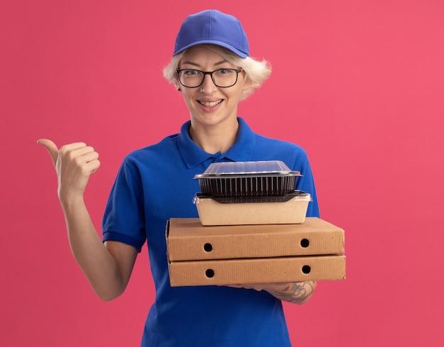 Giovane donna delle consegne in uniforme blu e cappello con gli occhiali che tengono le scatole della pizza e confezioni di cibo sorridendo allegramente indicando con il dito indice di lato sopra il muro rosa