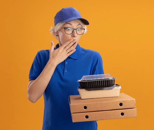 Young delivery woman in blue uniform and cap wearing glasses holding pizza boxes and food packages surprised and amazed covering mouth with hand over orange wall