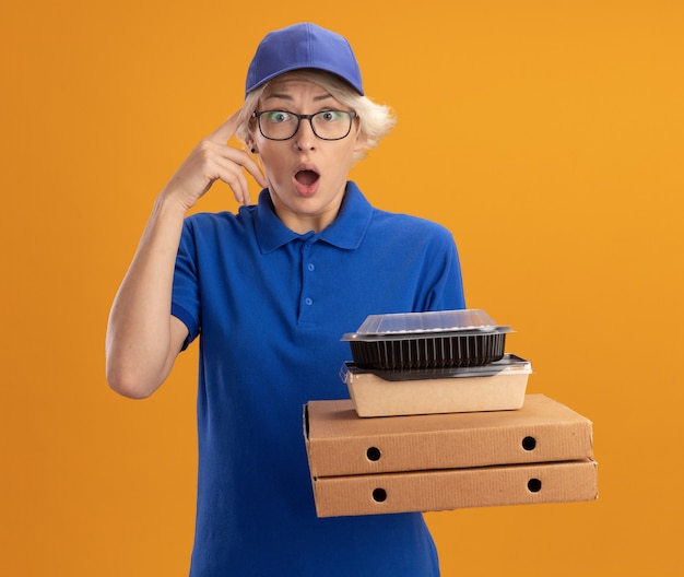 Giovane donna delle consegne in uniforme blu e berretto con gli occhiali che tengono le scatole della pizza e i pacchetti di cibo sorpresi sulla parete arancione