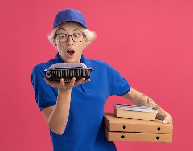 Giovane donna delle consegne in uniforme blu e berretto con gli occhiali che tengono scatole per pizza e confezioni di cibo guardando il pacchetto sorpreso e stupito sul muro rosa