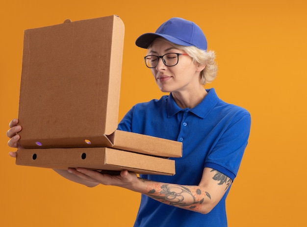 Giovane donna delle consegne in uniforme blu e berretto con gli occhiali che tengono le scatole della pizza aprendo una scatola inalando un aroma gradevole sulla parete arancione