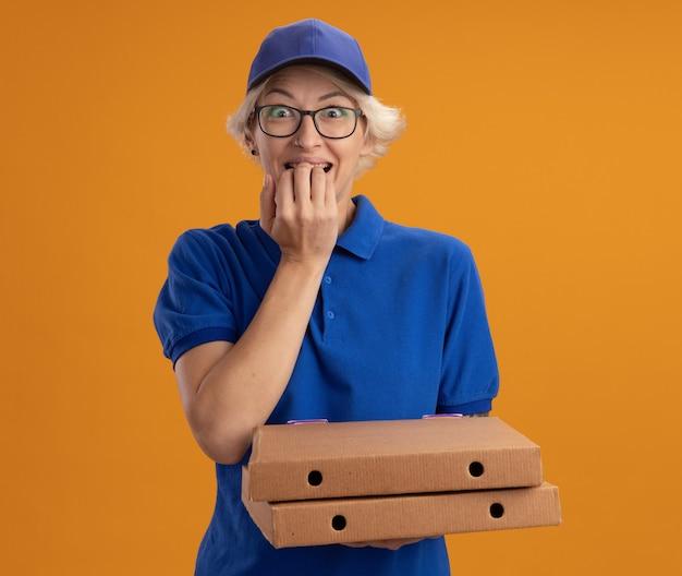 Giovane donna delle consegne in uniforme blu e berretto con gli occhiali che tengono le scatole per pizza stressati e nervosi chiodi mordaci sulla parete arancione