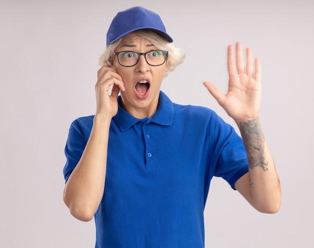 Giovane donna delle consegne in uniforme blu e cappuccio che indossa glesses parlando al telefono cellulare gridando in preda al panico con il braccio alzato in piedi sopra il muro bianco