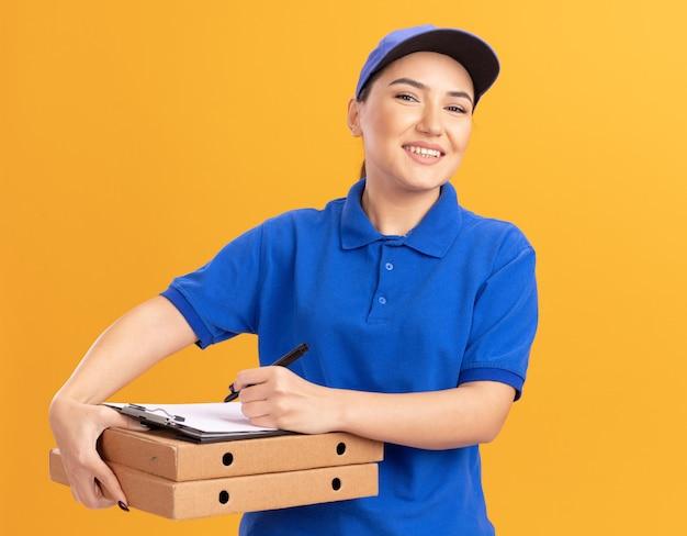Giovane donna di consegna in uniforme blu e cappuccio con appunti e matita che tiene le scatole per pizza guardando la parte anteriore sorridente allegramente in piedi sopra la parete arancione