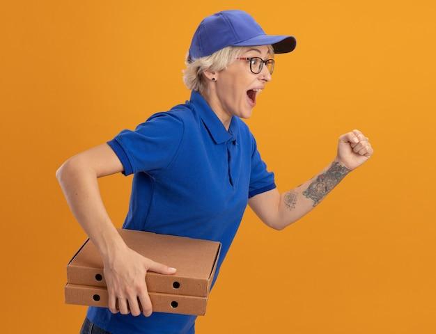 青い制服とキャップの若い配達の女性は、オレンジ色の壁を越えて顧客にピザボックスを配達するために急いで走っています