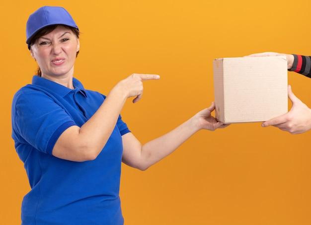 주황색 벽 위에 서있는 상자에서 검지 손가락으로 가리키는 상자 패키지를받는 동안 파란색 유니폼과 모자 느낌의 젊은 배달 여자