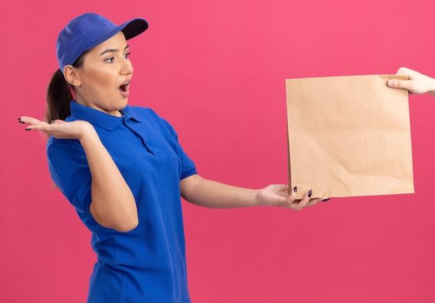 분홍색 벽 위에 서있는 종이 패키지를받는 동안 파란색 유니폼과 모자 느낌의 젊은 배달 여자