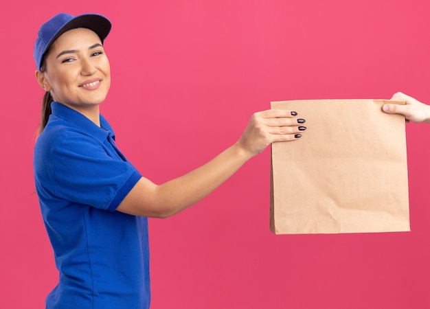 ピンクの壁の上に立ってフレンドリーな笑顔の顧客に紙のパッケージを与える青い制服とキャップの若い配達の女性