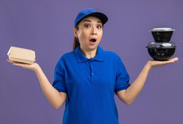 파란색 제복을 입은 젊은 배달 여자와 음식 패키지를 들고 모자는 깜짝 놀라게하고 보라색 벽 위에 서서 놀랐습니다.