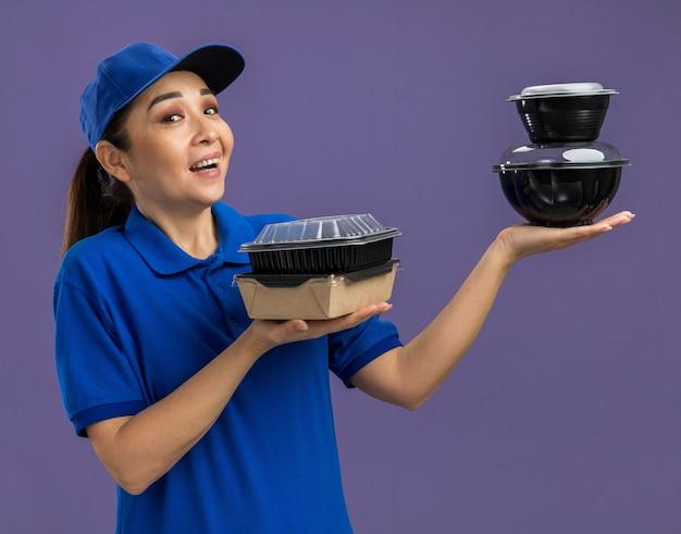 파란색 유니폼과 모자를 들고 젊은 배달 여자는 보라색 벽 위에 서 행복하고 쾌활한 웃는 서 음식 패키지
