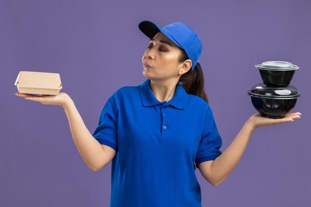 파란색 유니폼과 모자를 들고 젊은 배달 여자는 보라색 벽 위에 서있는 대답이없는 혼란스러워 보이는 음식 패키지를 들고