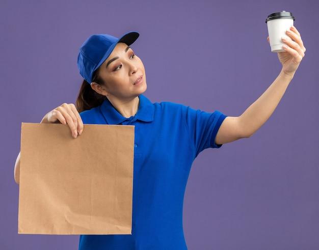 Молодая доставщица в синей форме и кепке держит бумажный пакет и бумажный стаканчик, заинтригованная чашкой с серьезным лицом, стоящим над фиолетовой стеной