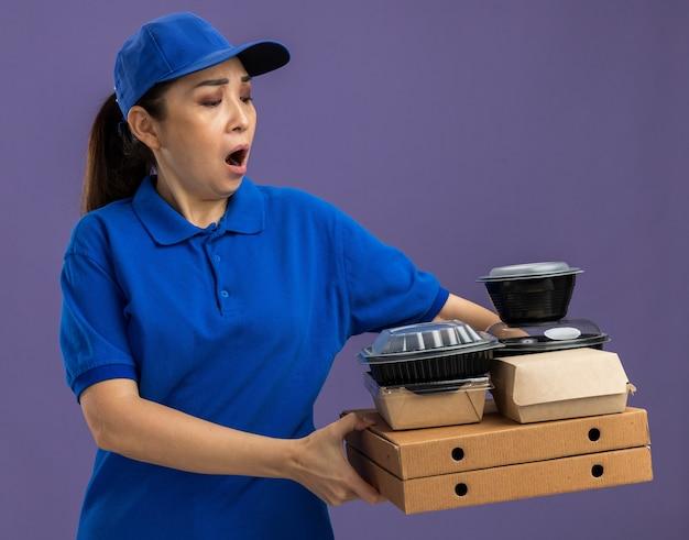 파란색 유니폼과 모자를 들고 젊은 배달 여자 피자 상자와 음식 패키지를 들고 깜짝 놀라게하고 보라색 벽 위에 서 놀란