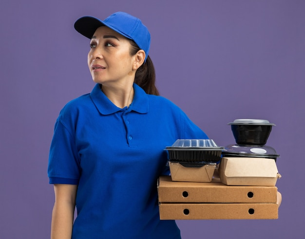 파란색 제복을 입은 젊은 배달 여자와 보라색 벽 위에 서있는 얼굴에 미소로 옆으로 찾고 피자 상자와 음식 패키지를 들고 모자