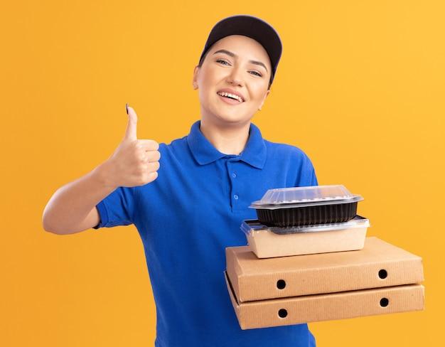 Молодая женщина-доставщик в синей форме и кепке держит коробки для пиццы и продуктовые пакеты, глядя вперед, весело улыбаясь, показывая большие пальцы руки вверх, стоя над оранжевой стеной