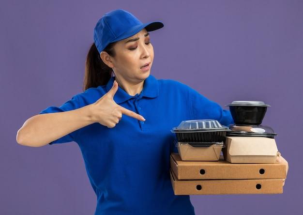 파란색 제복을 입은 젊은 배달 여자와 보라색 벽 위에 서있는 그들에게 검지 손가락으로 가리키는 피자 상자와 음식 패키지를 들고 모자