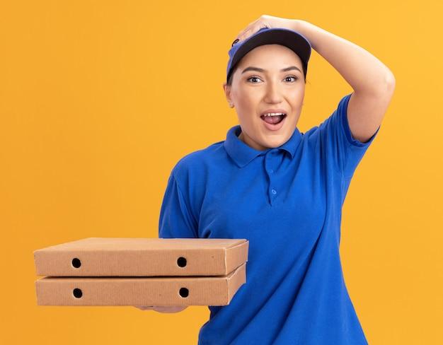オレンジ色の壁の上に立って驚いて驚いた正面を見てピザの箱を保持している青い制服と帽子の若い配達女性