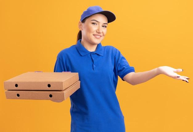 파란색 제복을 입은 젊은 배달 여자와 모자는 오렌지 벽 위에 서있는 그녀의 손의 팔을 제시하는 행복한 얼굴로 웃는 전면을보고 피자 상자를 들고