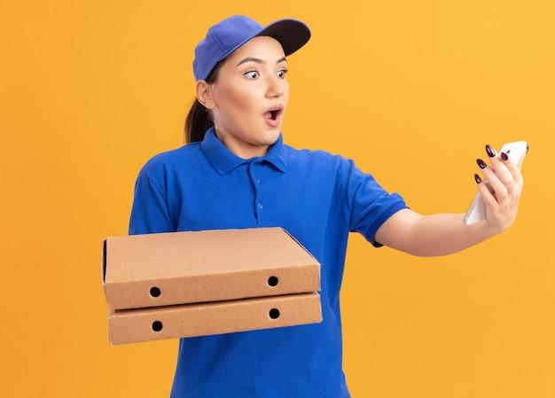 オレンジ色の壁の上に立って驚いて驚いている彼女のスマートフォンを見てピザの箱を保持している青い制服と帽子の若い配達の女性