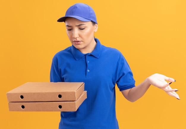파란색 유니폼과 모자를 들고 젊은 배달 여자 오렌지 벽 위에 서 혼란스러워하는 그들을보고 피자 상자를 들고