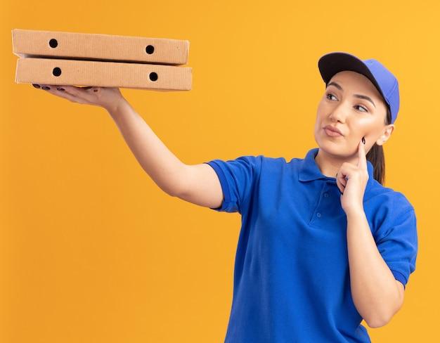 Молодая доставщица в синей форме и кепке держит коробки для пиццы, заинтригованно глядя на них, стоя у оранжевой стены