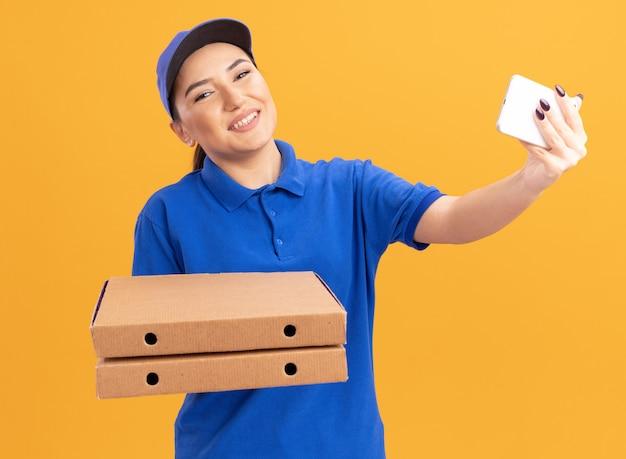 파란색 제복을 입은 젊은 배달 여자와 오렌지 벽 위에 유쾌하게 서있는 셀카를하고 스마트 폰을 사용하여 피자 상자를 들고 모자