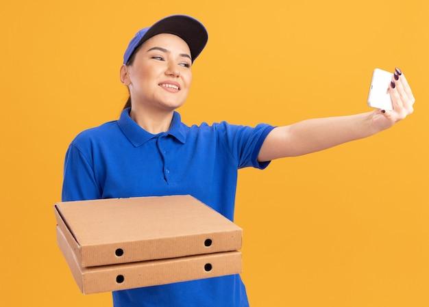 Молодая женщина-доставщик в синей форме и кепке держит коробки для пиццы, используя смартфон, делает селфи, весело улыбаясь, стоя над оранжевой стеной