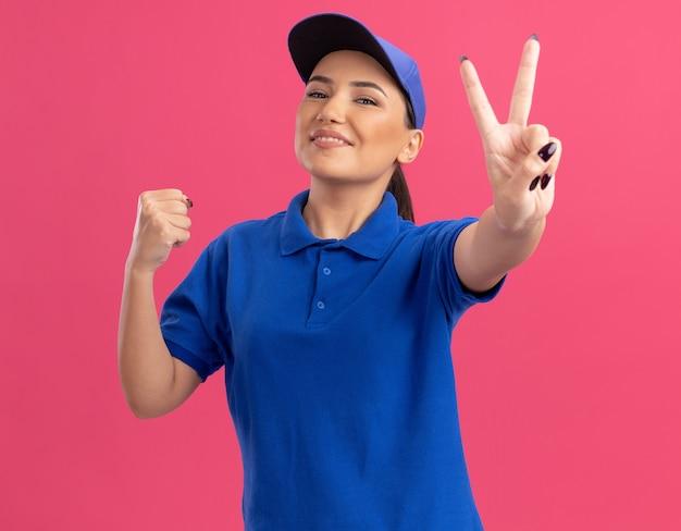 파란색 제복을 입은 젊은 배달 여자와 분홍색 벽 위에 유쾌하게 서있는 v 기호를 보여주는 주먹을 떨리는 앞을보고 모자