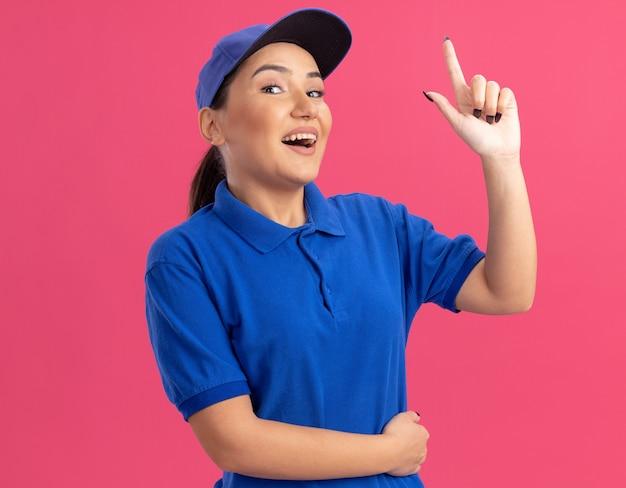 파란색 유니폼과 모자에 젊은 배달 여자는 분홍색 벽 위에 새로운 아이디어가 서있는 전면 행복하고 긍정적 인 보여주는 검지 손가락을보고