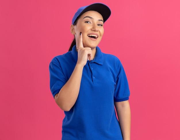 파란색 제복을 입은 젊은 배달 여자와 분홍색 벽 위에 유쾌하게 행복하고 긍정적 인 서있는 정면을보고 모자