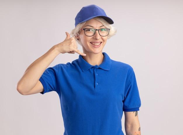 파란색 제복을 입은 젊은 배달 여자와 모자가 흰 벽 위에 서있는 제스처를 만드는 전화를 찾고
